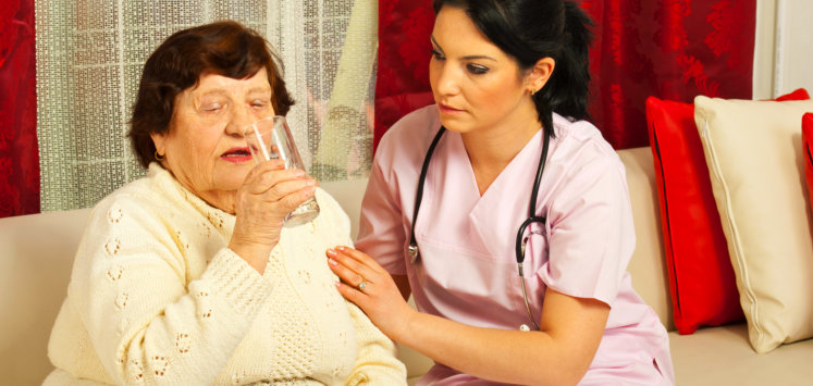 nurse assisting elderly woman in drinking water